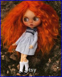 Doll custom Blythe. Long red natural curly goat hair, in a sea dress and panama hat, listening to the sound of the sea in a shell